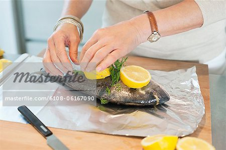 Elderly woman preparing seafood in a kitchen Stock Photo - Premium Royalty-Free, Image code: 6108-06167090