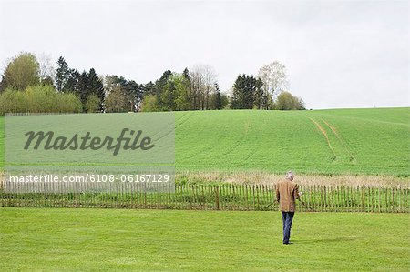 Man using a mobile phone in a field Stock Photo - Premium Royalty-Free, Image code: 6108-06167129