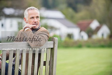 Man sitting on a bench and thinking in a park Stock Photo - Premium Royalty-Free, Image code: 6108-06167133