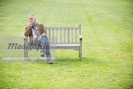 Man sitting on a bench and thinking in a park Stock Photo - Premium Royalty-Free, Image code: 6108-06167139