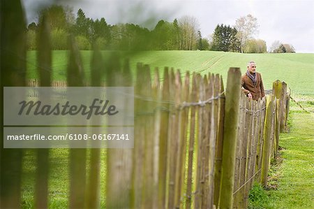 Man standing by fence in a field Stock Photo - Premium Royalty-Free, Image code: 6108-06167141