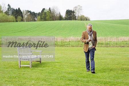Man using a mobile phone in a field Stock Photo - Premium Royalty-Free, Image code: 6108-06167145