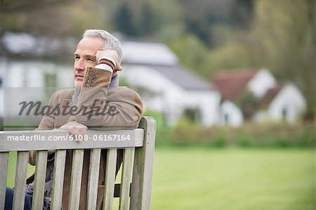 Man sitting on a bench and thinking in a park Stock Photo - Premium Royalty-Free, Image code: 6108-06167164