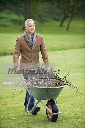 Man collecting firewood in a park Stock Photo - Premium Royalty-Free, Image code: 6108-06167173
