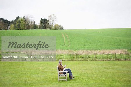 Man sitting on the bench and using a mobile phone in a field Stock Photo - Premium Royalty-Free, Image code: 6108-06167177