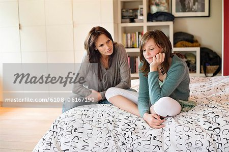 Woman looking at her sad daughter in the bedroom Stock Photo - Premium Royalty-Free, Image code: 6108-06167190