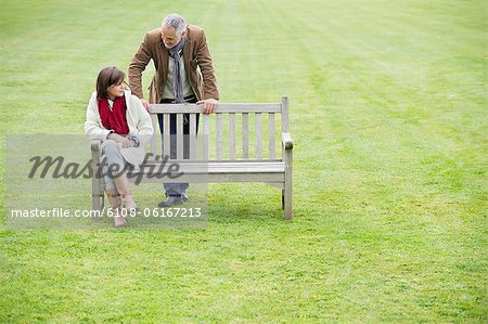 Man sitting with his daughter on a bench in a park Stock Photo - Premium Royalty-Free, Image code: 6108-06167213