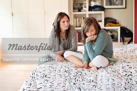 Woman scolding her daughter in the bedroom Stock Photo - Premium Royalty-Free, Image code: 6108-06167232