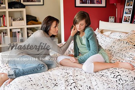 Woman consoling her sad daughter in the bedroom Stock Photo - Premium Royalty-Free, Image code: 6108-06167233