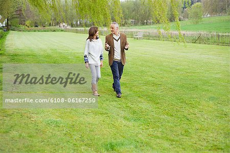 Man discussing with his daughter during walk in a park Stock Photo - Premium Royalty-Free, Image code: 6108-06167250