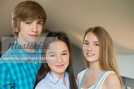 Portrait of a teenage boy with his two sisters smiling Stock Photo - Premium Royalty-Free, Image code: 6108-06167253