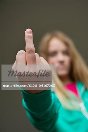 Girl showing middle finger Stock Photo - Premium Royalty-Free, Image code: 6108-06167263
