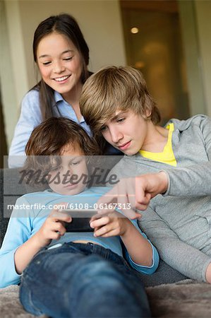 Boy using a cellphone with his brother and sister at home Stock Photo - Premium Royalty-Free, Image code: 6108-06167313