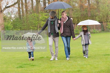 Family walking with umbrellas in a park Stock Photo - Premium Royalty-Free, Image code: 6108-06167317
