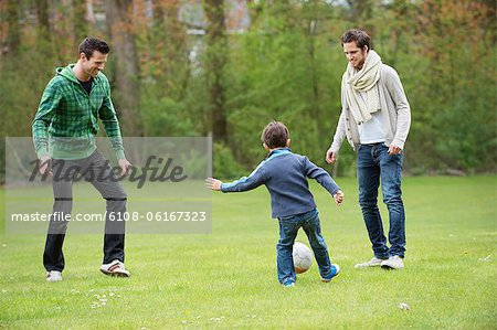 Boy playing soccer with two men in a park Stock Photo - Premium Royalty-Free, Image code: 6108-06167323