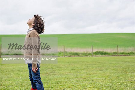 Boy daydreaming in a field Stock Photo - Premium Royalty-Free, Image code: 6108-06167342