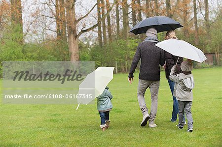 Family walking with umbrellas in a park Stock Photo - Premium Royalty-Free, Image code: 6108-06167345