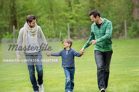Boy walking with two men in a park Stock Photo - Premium Royalty-Free, Image code: 6108-06167348