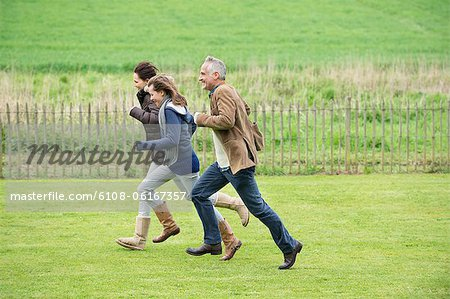 Happy family running in a field Stock Photo - Premium Royalty-Free, Image code: 6108-06167357