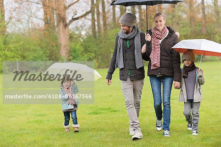 Family walking with umbrellas in a park Stock Photo - Premium Royalty-Free, Image code: 6108-06167366