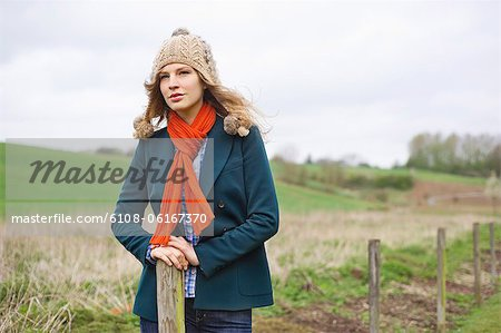 Beautiful woman standing in a field Stock Photo - Premium Royalty-Free, Image code: 6108-06167370