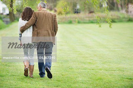 Man walking with his daughter in a park Stock Photo - Premium Royalty-Free, Image code: 6108-06167390