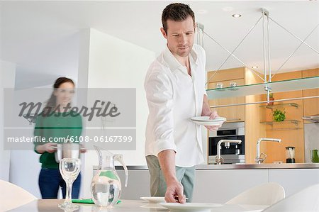 Couple preparing to serve dinner Stock Photo - Premium Royalty-Free, Image code: 6108-06167399