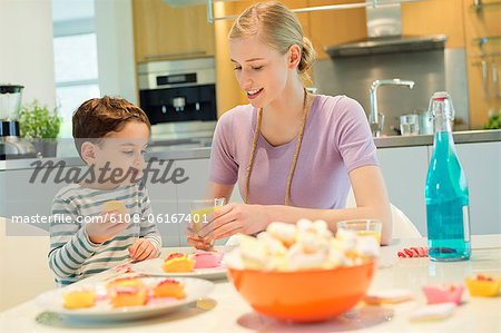 Woman and son at breakfast table Stock Photo - Premium Royalty-Free, Image code: 6108-06167401