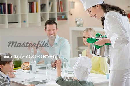 Little boy assisting his mother in serving dinner Stock Photo - Premium Royalty-Free, Image code: 6108-06167402