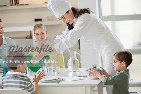 Little boy assisting his mother in serving dinner Stock Photo - Premium Royalty-Free, Image code: 6108-06167411