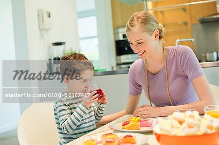 Woman and son at breakfast table Stock Photo - Premium Royalty-Free, Image code: 6108-06167417