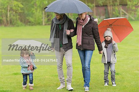 Family with umbrellas in a park Stock Photo - Premium Royalty-Free, Image code: 6108-06167542