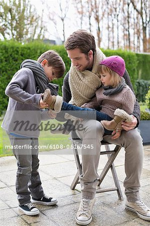 Boy putting shoe on his sister sitting in her father's lap Stock Photo - Premium Royalty-Free, Image code: 6108-06167545