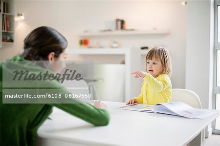 Woman teaching her daughter at home Stock Photo - Premium Royalty-Free, Image code: 6108-06167550