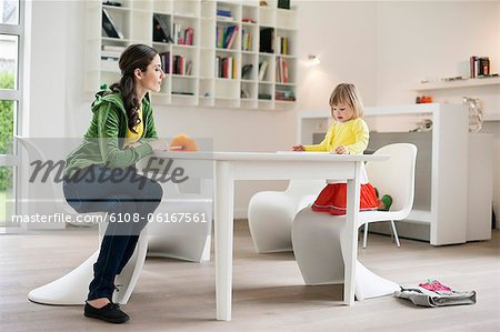 Woman teaching her daughter at home Stock Photo - Premium Royalty-Free, Image code: 6108-06167561