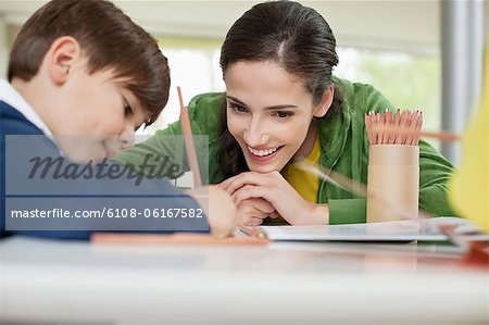 Woman teaching her son at home Stock Photo - Premium Royalty-Free, Image code: 6108-06167582