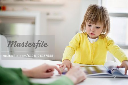 Woman teaching her daughter at home Stock Photo - Premium Royalty-Free, Image code: 6108-06167588