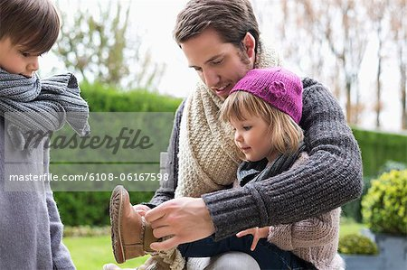 Man putting on shoe to his daughter Stock Photo - Premium Royalty-Free, Image code: 6108-06167598