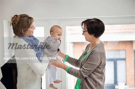 Woman giving her daughter to nanny Stock Photo - Premium Royalty-Free, Image code: 6108-06167648