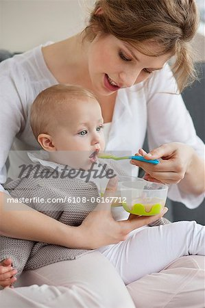 Woman feeding her daughter Stock Photo - Premium Royalty-Free, Image code: 6108-06167712