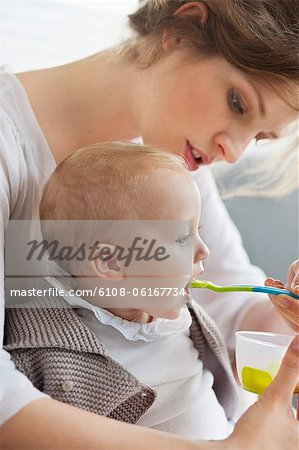 Woman feeding her daughter Stock Photo - Premium Royalty-Free, Image code: 6108-06167734
