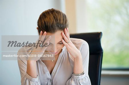 Close-up of a businesswoman suffering from a headache in an office Stock Photo - Premium Royalty-Free, Image code: 6108-06167843