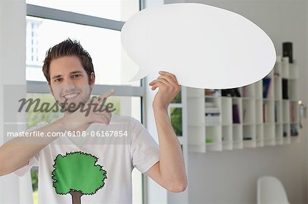 Man holding a speech bubble Stock Photo - Premium Royalty-Free, Image code: 6108-06167854