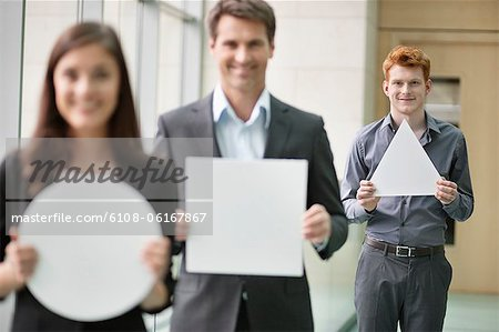 Business executives holding geometrical shaped placards in an office Stock Photo - Premium Royalty-Free, Image code: 6108-06167867