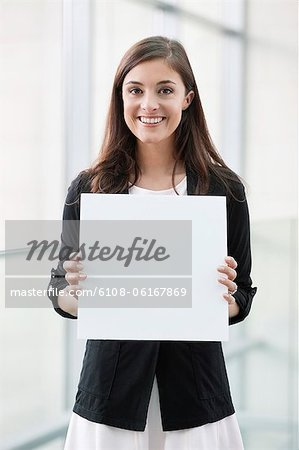 Portrait of a businesswoman holding a blank placard and smiling in an office Stock Photo - Premium Royalty-Free, Image code: 6108-06167869