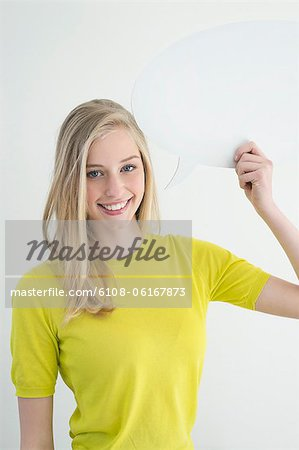 Woman holding a speech bubble and smiling Stock Photo - Premium Royalty-Free, Image code: 6108-06167873