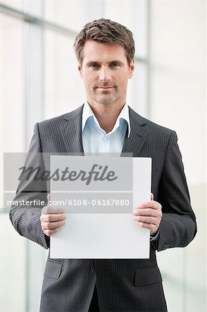 Businessman holding a blank placard in an office Stock Photo - Premium Royalty-Free, Image code: 6108-06167880