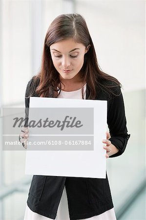 Businesswoman holding a blank placard in an office Stock Photo - Premium Royalty-Free, Image code: 6108-06167884
