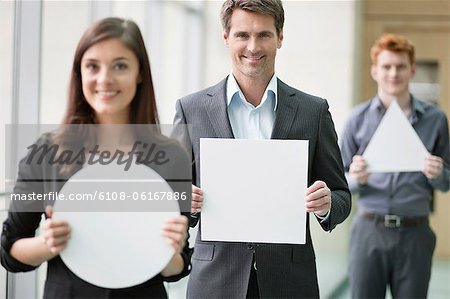 Business executives holding geometrical shaped placards in an office Stock Photo - Premium Royalty-Free, Image code: 6108-06167886