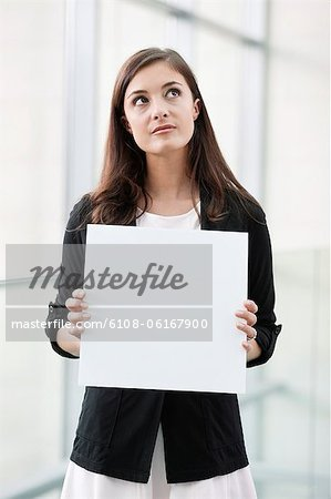 Businesswoman holding a blank placard and thinking in an office Stock Photo - Premium Royalty-Free, Image code: 6108-06167900
